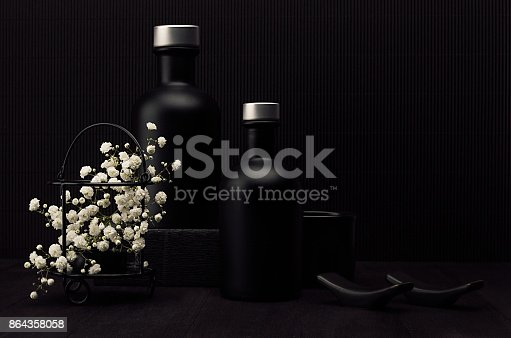 847096968 istock photo Noir exquisite home decor with blank black cosmetics bottles, white small flowers on dark wood board, mock up. 864358058