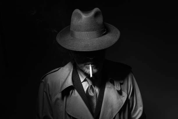 Noir film character smoking a cigarette Man with fedora hat and trench coat smoking a cigarette in the dark, 1950s noir film character gangster stock pictures, royalty-free photos & images
