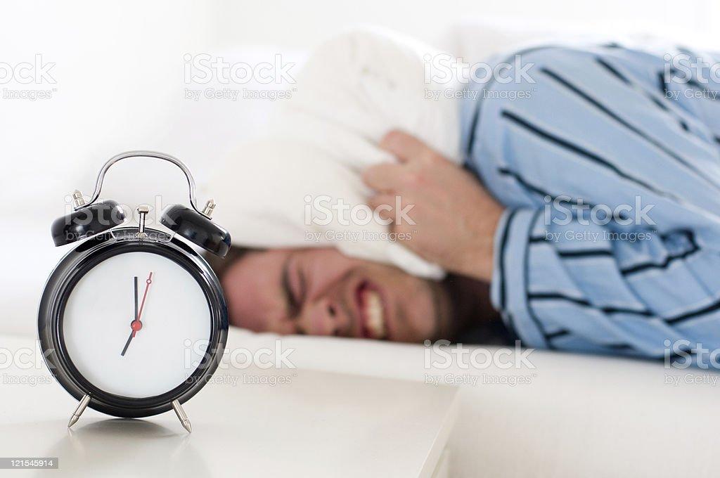 Noisy Alarm Clock wakes tired man wearing pajamas royalty-free stock photo