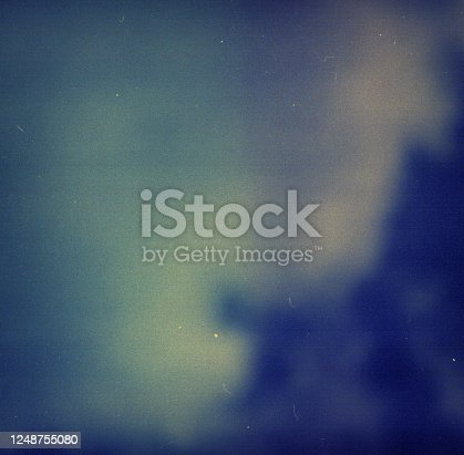 1143033009 istock photo Noisy blue film frame with scratches, dust and grain 1248755080