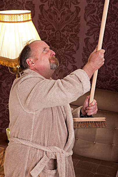 Noisy neighbours Mature man hitting the ceiling with a broom to warn the noisy upstairs neighbours broom stock pictures, royalty-free photos & images
