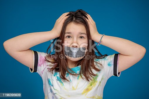 A noisy teenage girl in a self-made colorful t-shirt silenced with silver tape. Studio shot on blue background.