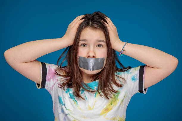noisy teenager girl silenced with a mouth sealed with silver tape and head in hands stock photo