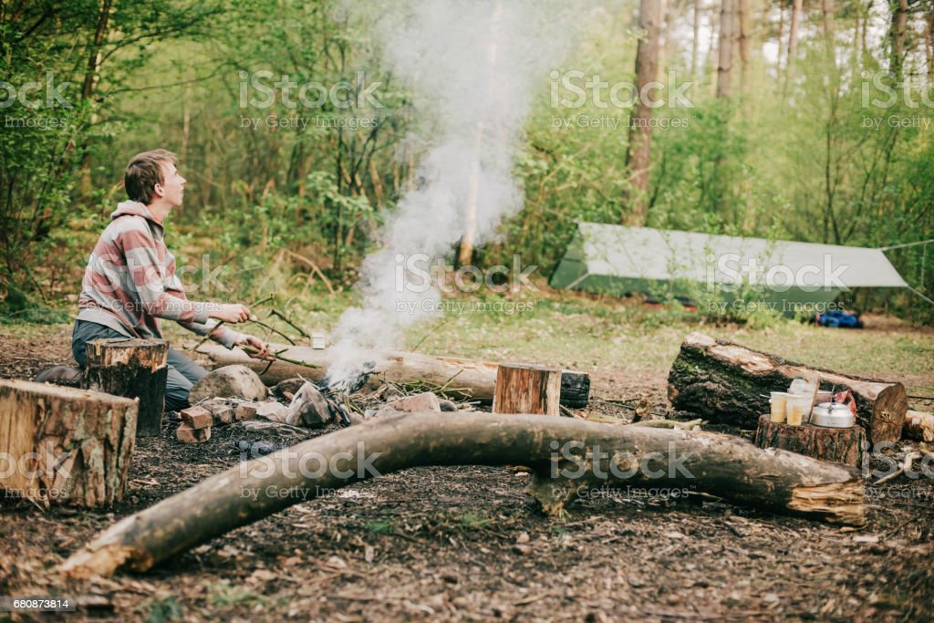 Nomad creating a campfire in spring forest. royalty-free stock photo