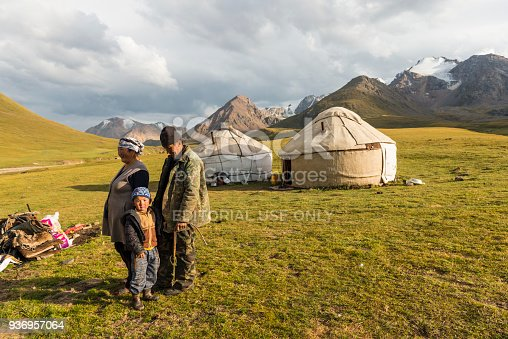Scenic view on nomad family, women, man and a boy at lake Kol-Ukok against two yurts and green hill and mountain range on sunny day.