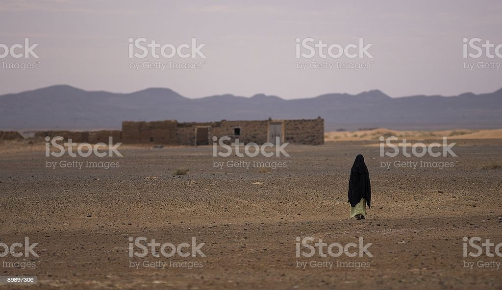 Nomad walking across a rocky desert royalty-free stock photo