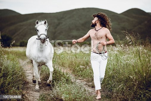 Nomadic Rancher Leading And Training Horse Through Meadow