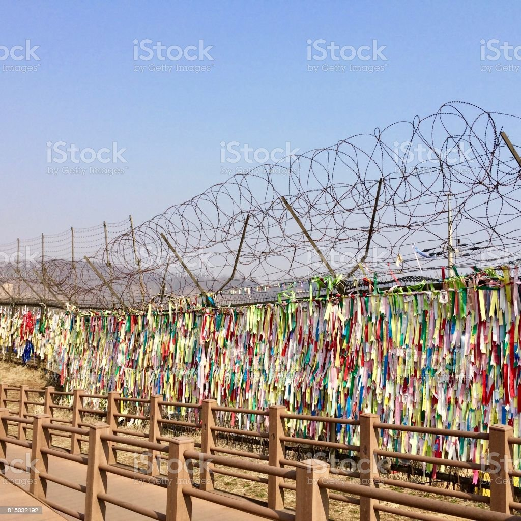 No-man's-land between the border of North & South Korea (Asia) in Imjingak: flags, barb wire fence, camera, drought, brown sand desert, hills / mountains separate the demilitarized war zone stock photo