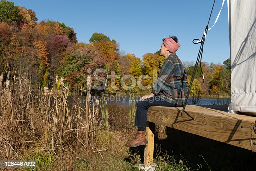 One mixed race non binary female of Persian and Norwegian descent with short hair in a gingham headscarf, a plaid shirt, jeans and boots sits on a simple wooden porch lakeside on a autumn day in the Catskill Mountains while at a glamping campsite on the Stone Ridge Orchard in upstate New York.