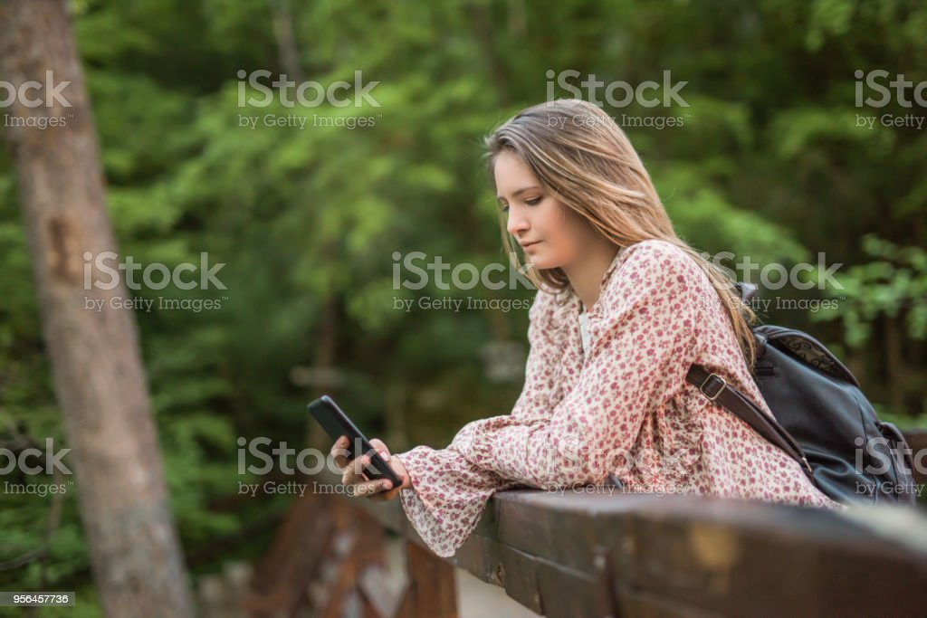 Non urban scene of young teenage girl texting a message. stock photo