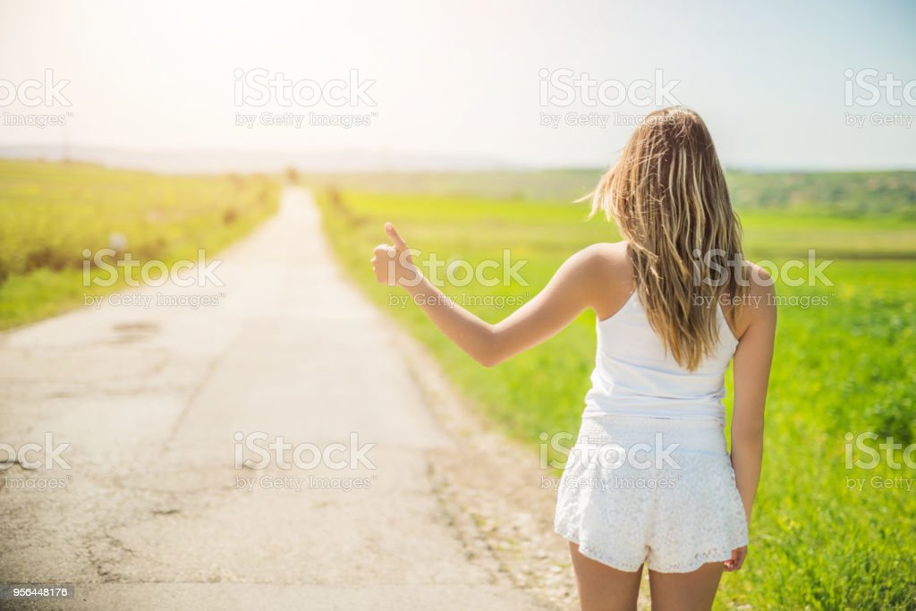 Non urban scene of young woman hitchhiking next to a road. stock photo