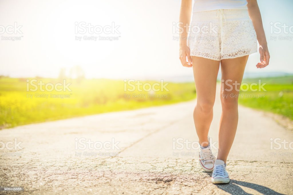 Non urban scene of young woman walking on the road. stock photo