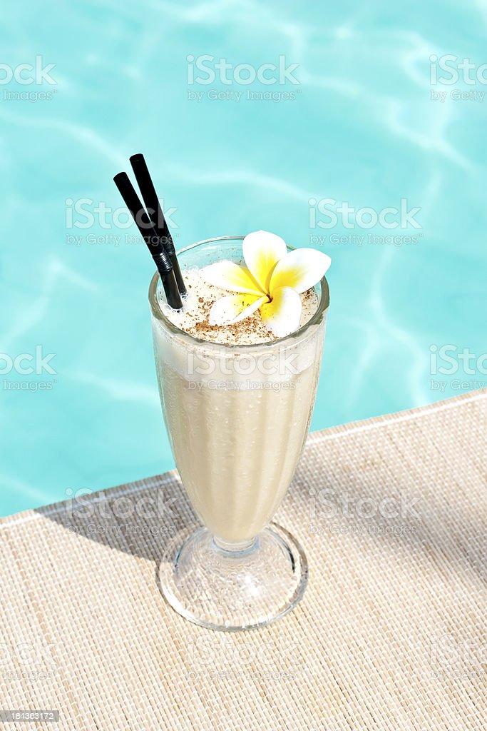non-alcoholic milkshake cocktail near waterpool on the mat stock photo