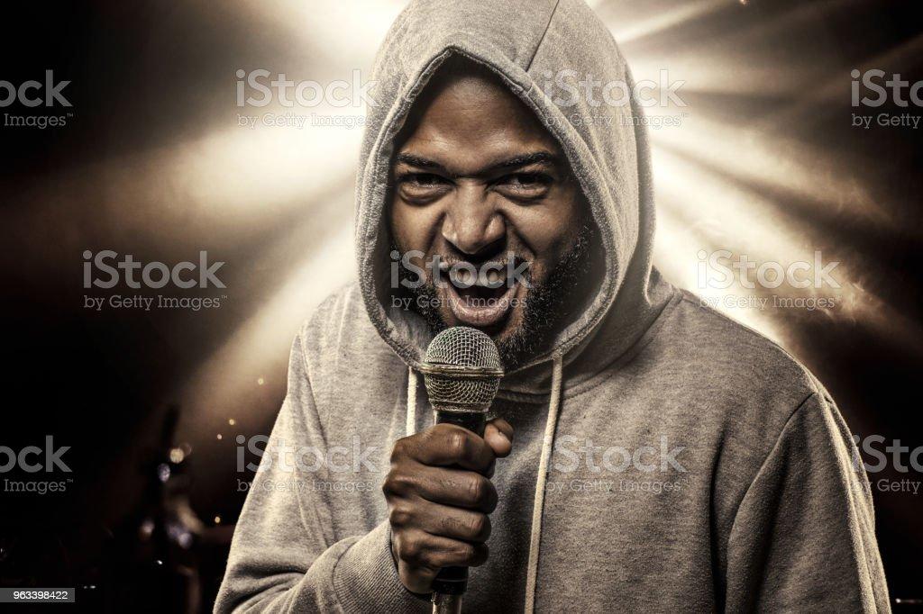Niekaukaski afrykański emcee rapuje do mikrofonu przed światłami koncertowymi - Zbiór zdjęć royalty-free (Rap)