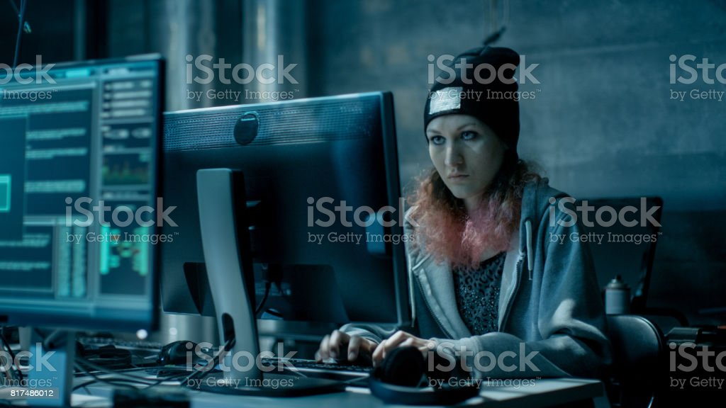 Nonconformist Teenage Hacker Girl Attacks and Hacks Corporate Servers with Virus. Room is Dark, Neon and Has Many Displays and Cables. stock photo
