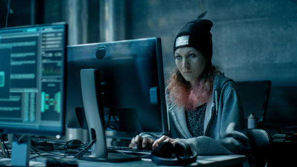nonconformist teenage hacker girl attacks and hacks corporate servers with virus. room is dark, neon and has many displays and cables. - hacker stock photos and pictures