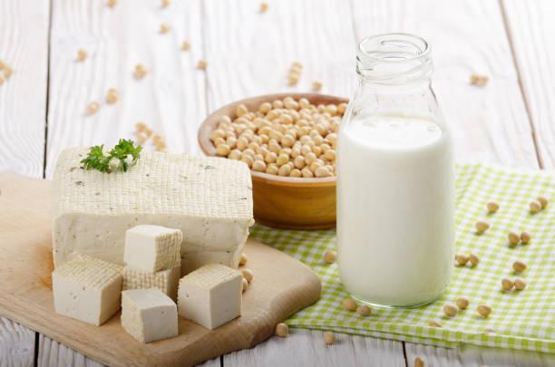 niet-zuivel alternatieven sojamelk of yoghurt in glazen fles en tofu op witte houten tafel met sojabonen in de kom opzij - tofoe stockfoto's en -beelden
