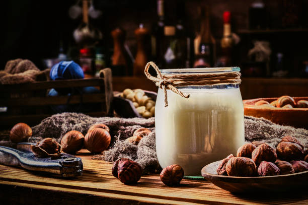 Non-dairy hazelnut milk in glass and jar with nuts in old fashioned rustic kitchen stock photo