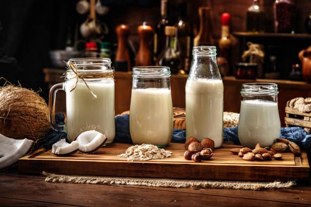 Variété non laitière de laits non laitiers: noix de coco, avoine, noisettes et amandes dans des verres à boire. Placé sur une table dans la cuisine démodée - Photo