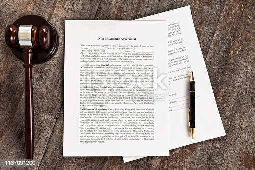Close up of a generic non-disclosuer agreement with a pen and a gavel.