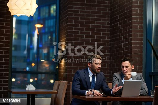 Confident business consultant explaining entrepreneur how to run business and showing presentation on laptop over coffee