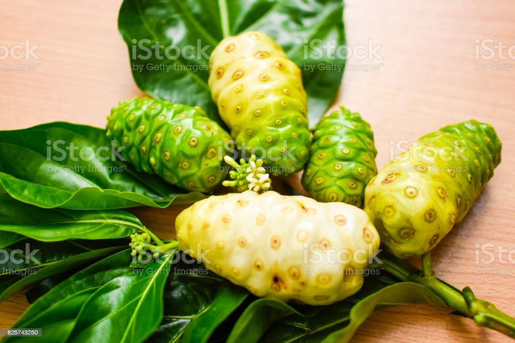 Noni fruit with leaf on  wooden table. Zoom in stock photo