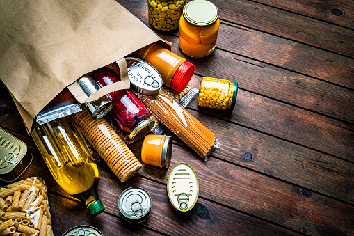 High angle view of a large group of multicolored non-perishable canned goods, conserves, sauces, crackers, cereals, beans, and oils coming out a brown paper bag shot on wooden table. The composition includes cooking oil bottle, pasta, beans, preserves and tins. High resolution 42Mp studio digital capture taken with SONY A7rII and Zeiss Batis 40mm F2.0 CF lens