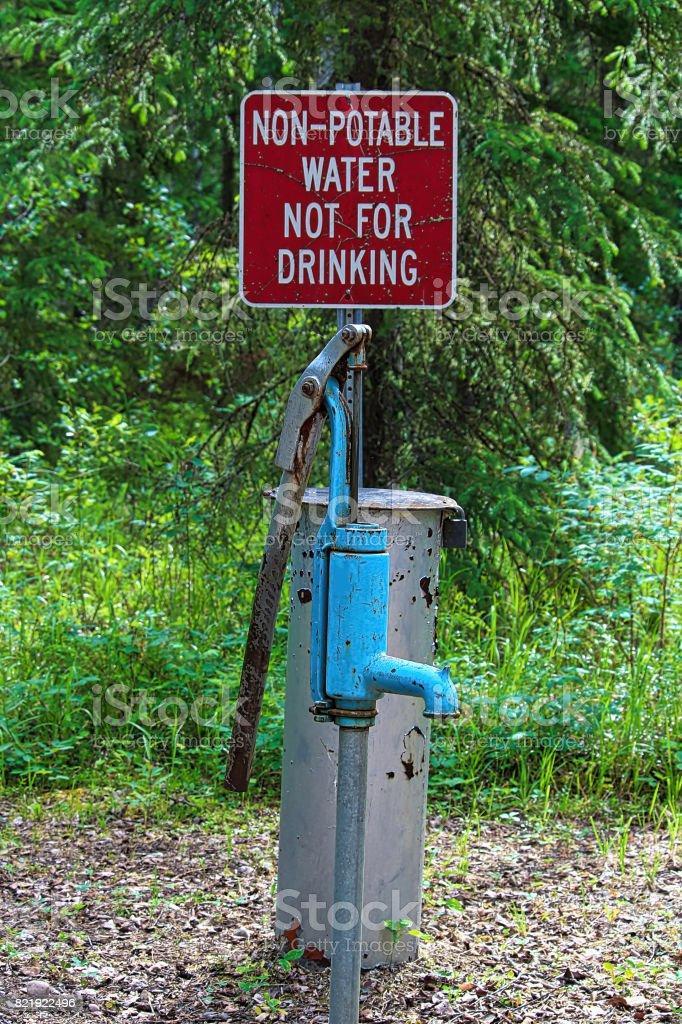 A non-potable water, not for drinking sign near a pump stock photo