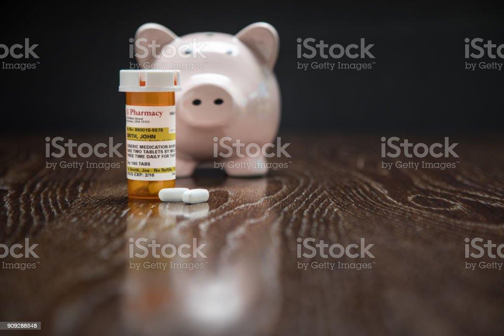 Non-Proprietary Prescription Medicine Bottle, Pills and Piggy Bank on Reflective Wooden Surface. stock photo