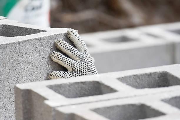 rutschhemmendes sicherheit handschuh auf hand stapeln konkrete häuserblocks - betonblock wände stock-fotos und bilder