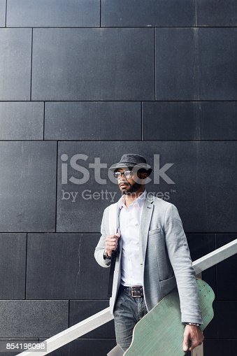 Contemplative hipster young businessman in fashionable dress moving on skateboard around city