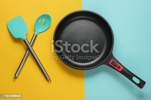 Non-stick pan with cooking spatula on blue yellow background. Cooking minimalism concept. Studio shot. Top view