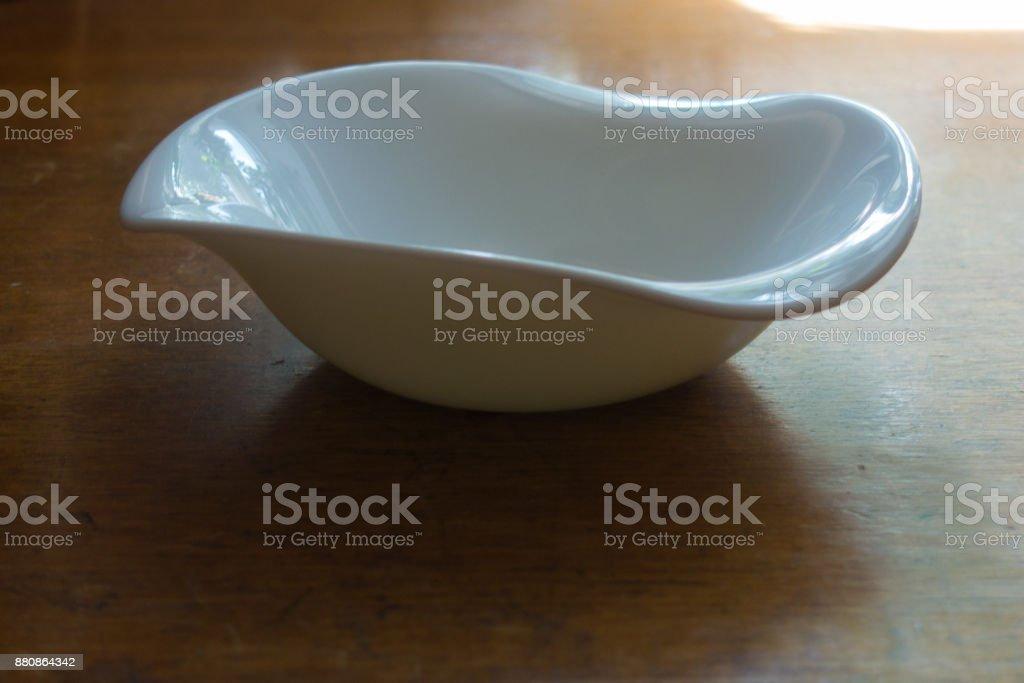 Non-symmetric empty ceramic bowl on wooden table stock photo