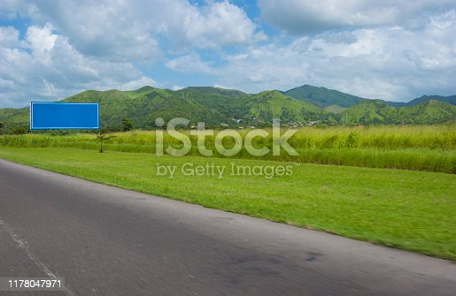 View of empty non-urban road with outdoors advertising blue board or road sign with copy space.