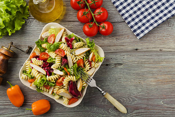 noodle salad with green salad, tomatoes and roasted chicken. - gesunde huhn pasta stock-fotos und bilder