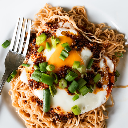 Asian noodles with over easy egg, the runny yolk mixing with the chili oil and sauce.  Fresh green onion garnishes the dish.