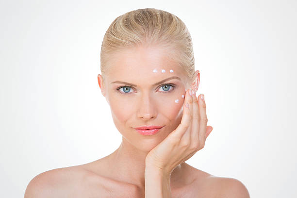 nordic girl applying salve on her face stock photo