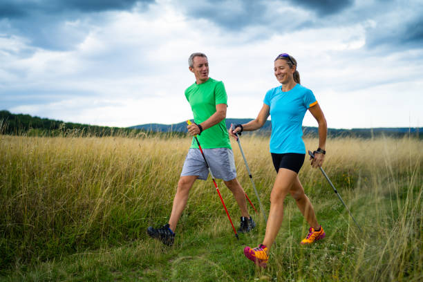 nordic walking couple in grassland active smiling middle aged couple doing nordic walking sport in grassland with  shallow focus cloudy overcast sky dark clouds front view nordic walking stock pictures, royalty-free photos & images