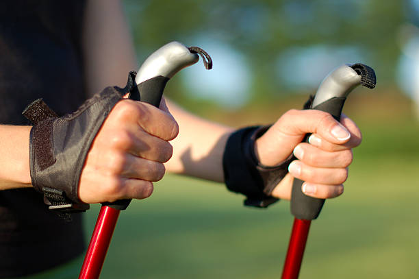 Nordic walking in summer Closeup of woman's hands holding nordic walking poles nordic walking stock pictures, royalty-free photos & images