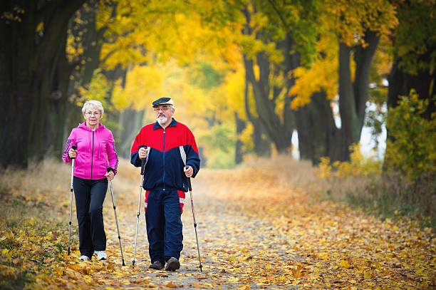 Nordic walking senior couple making nordic walking in the park nordic walking stock pictures, royalty-free photos & images