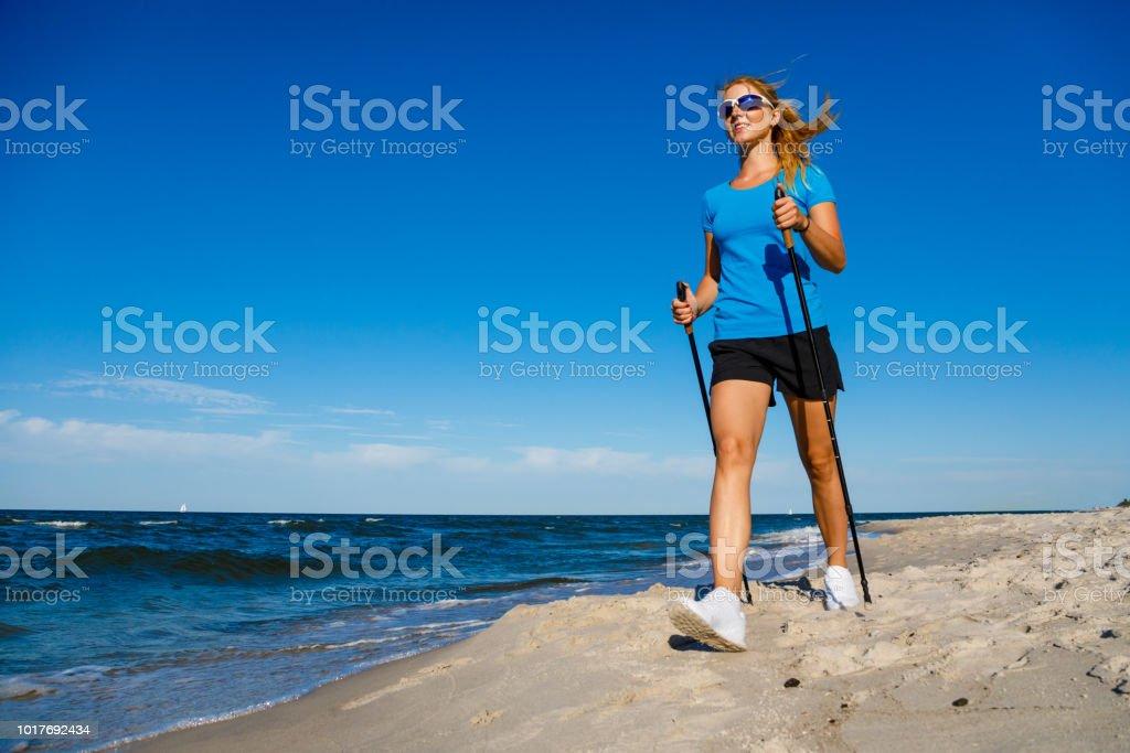 Nordic walking - woman training at seaside Nordic walking - woman training at seaside 20-29 Years Stock Photo