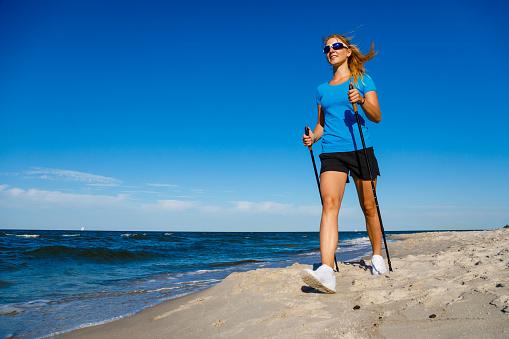 Nordic Walking Woman Training At Seaside Stock Photo - Download Image Now