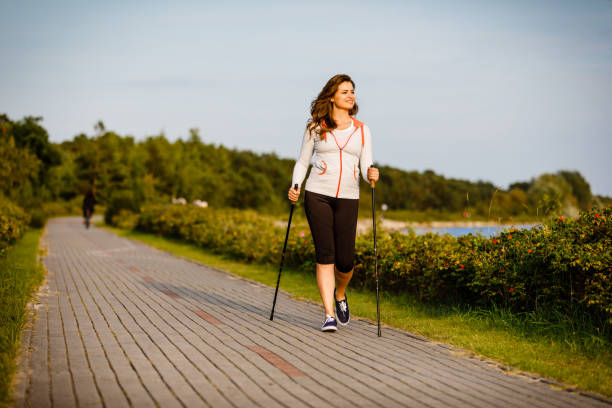 Nordic walking - young woman training outdoor Summer joy - people walking outdoor nordic walking stock pictures, royalty-free photos & images