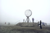 Nordkapp, Norway - 26 July, 2017: Nordkapp edge cliffhanger with the globus monument with tourist around in summer foggy day. Nord cape, Finnmark, Mageroya island.