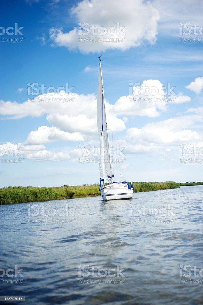 Norfolk Broads sail boat sailing down a river stock photo