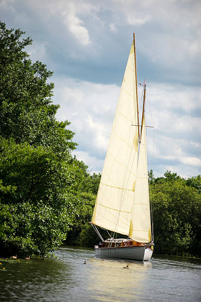 Norfolk Broads sail boat sailing on a river stock photo