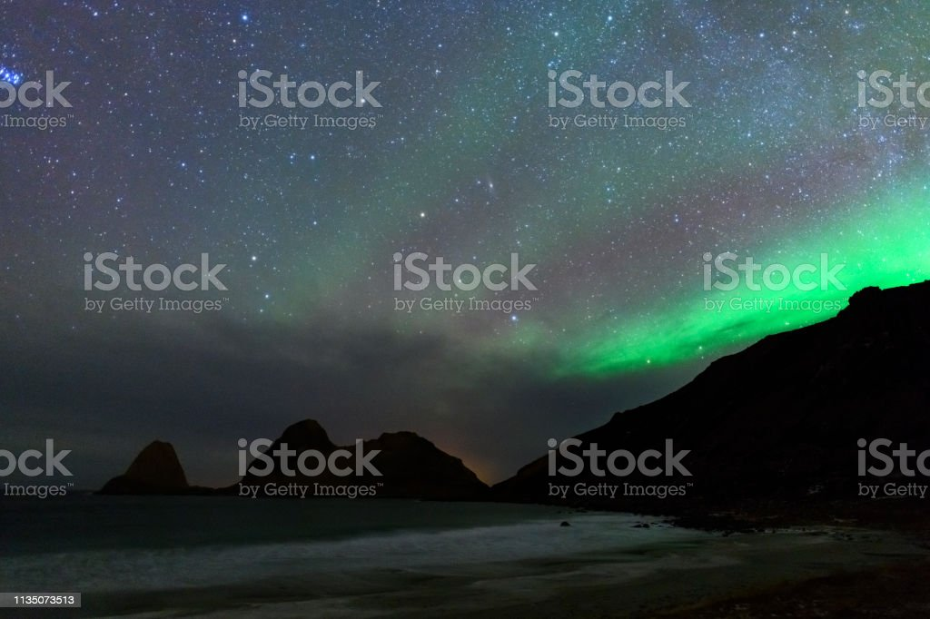 Norhtern Lights or aurora over Nykvag beach with a starry sky in...