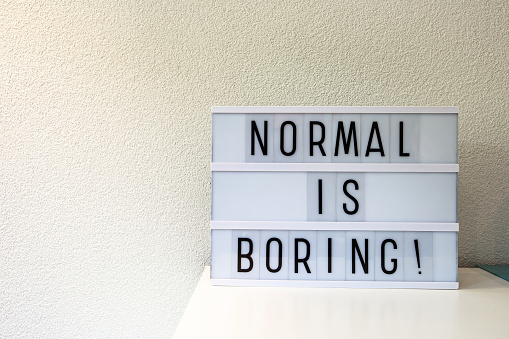 istock Normal is boring written in Light box home decoration, motivational sign retro home, space for text 1263653599