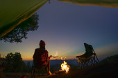 silhouette of woman traveller camping in campsite with cooking meal dinner
