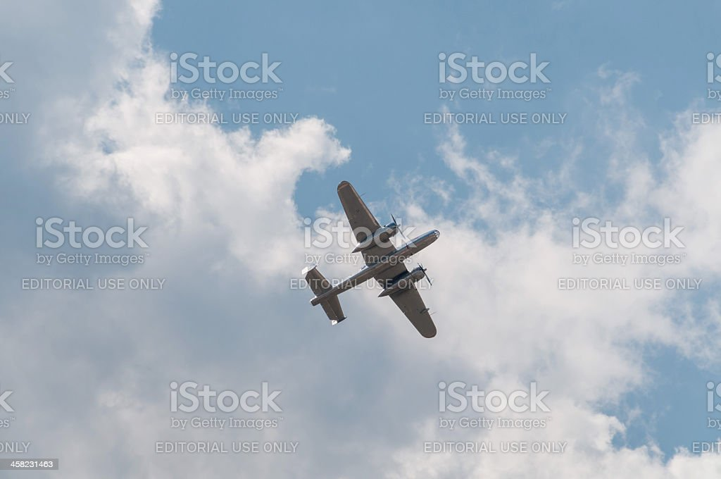 North American B-25 Mitchell bomber flies against cloudy sky background stock photo